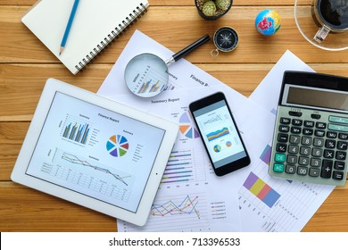 Office desk table with tablet,business documents,smart phone,pencil,glasses,calculator and cup of coffee.Top view with copy space.