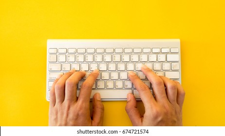 Office desk table Top view with keyboard and hand yellow background