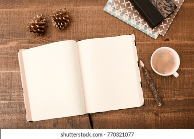 Office desk table. Top view with blank notebook, pencil and coffee on wooden table background. Top view with copy space