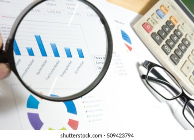 Office Desk with Tools and Notes About Digital Marketing. Study financial report which including of finance summary, market research, analytics & statistics conclusion and marketing summary report.