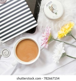 Office desk top view: notebook, coffee, flowers, handcream and tablet. Lifestyle blogger photo. Girly white flatlay