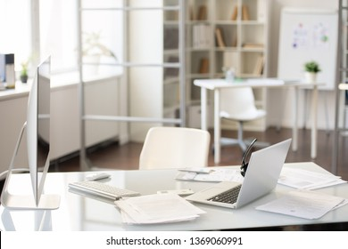 Office desk with two computers on table with report papers, hands-free device on laptop