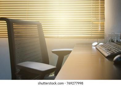 Office desk. Wooden desk and chair on venetian blinds background