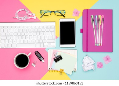 Office Desk Working Space Flat Lay. Top view photo of workspace with keyboard, notepad and coffee on pastel colored background. Student working desk concept.