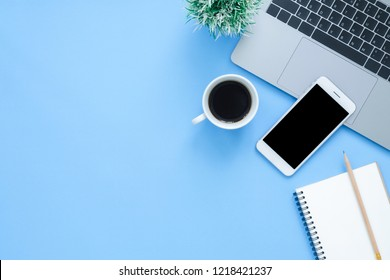 Office desk working space - Flat lay top view mockup photo of working space with laptop, smartphone, coffee up and notebook on blue pastel background. Pastel blue color background working desk concept