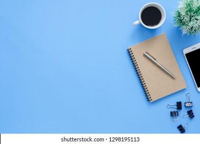 Office desk working space - Flat lay top view mockup photo of working space with tablet, phone, coffee cup and notebook on blue pastel background. Pastel blue color copy space working desk concept.