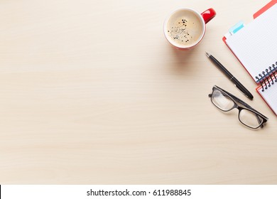 Office desk workplace with coffee cup, notepad and glasses on wooden background. Top view with copy space
