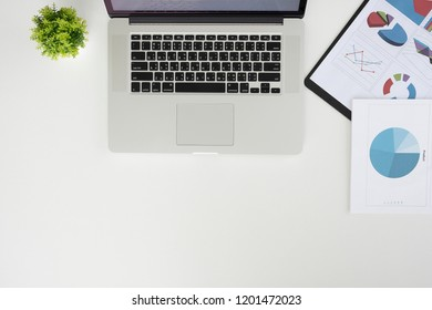 Office desk workplace with laptop, charts and coffee on wooden table. Top view with copy space