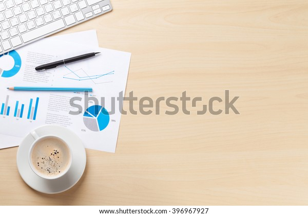 Office desk workplace with pc, charts and coffee on wooden table. Top view with copy space
