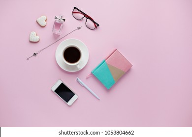 Office desk. Workspace with cofee, notebook, mobile phone, women's fashion accessories on pink background. Flat lay concept for magazines, websites, media.