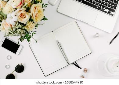Büroarbeitsplatz mit Computer, geöffnetes Notebook, Blumenstrauß und Schreibtisch auf weißem Tisch. Flachlage, Draufsicht