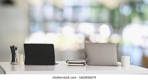 Office desk workspace with laptop, tablet and office supplies on white table in modern office with blurred background. Concept of orderly workplace.