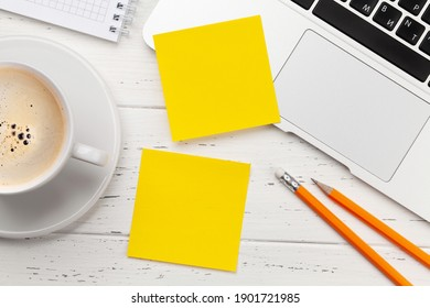 Office desk with yellow stickers, coffee and laptop. Remote office and work from home concept. Top view flat lay with copy space