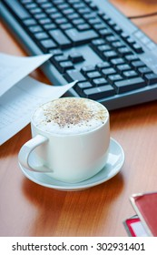 Office desktop with cappuccino coffee cup and work essential tools