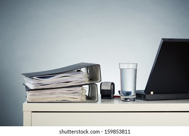 Office desktop with folders, a computer and a glass of water.