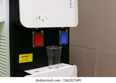 Office electric water cooler with empty plastic cup