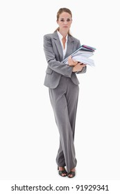 Office employee with pile of paperwork against a white background