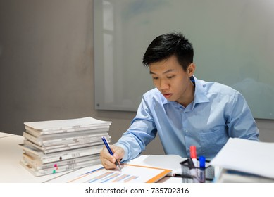 Office employee reading sales report and writing notes