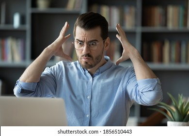 Office employee sit at desk looks at laptop screen feels angry due reading bad email news, problems with computer, lost unsaved information, troubles at work or device, malfunction need repair concept