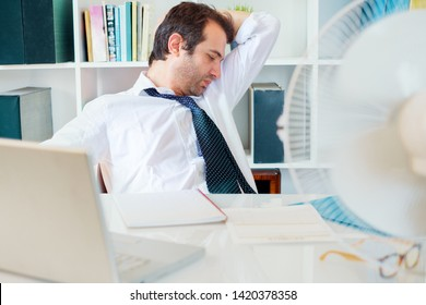 Office employee sweating and smelling and notices his sweat under armpit