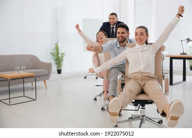 Office employees riding chairs at workplace. Space for text