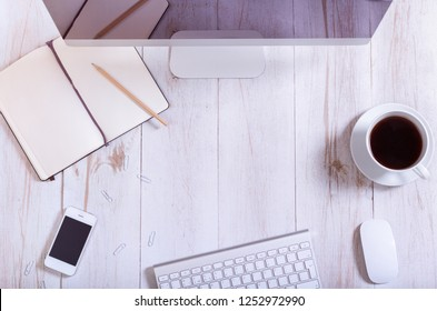 Office equipment at workplace concept, pc computer monitor smart phone, keyboard, open notebook and coffee on white wooden table background, modern work desk business supplies, top view, copy space