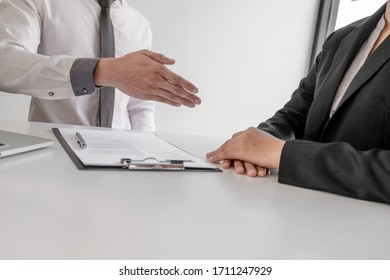 Office executives are interviewing job applicants in the meeting room.