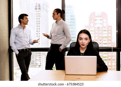 Office gossip concept. Two handsome man talking about beautiful woman in the front while she is working on a laptop and over heard them. Office chit chat, rumour, verbal assault concept.