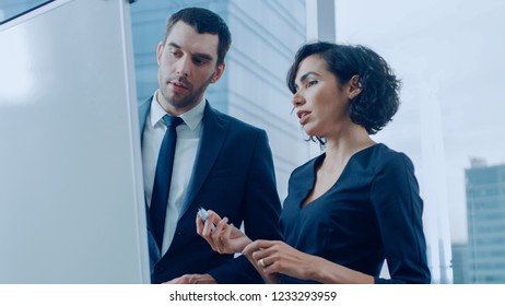 In the Office Handsome Businessman and Beautiful Businesswoman Have Discussion while Using Whiteboard. Planning Marking Expansion, Consulting Data and Making Graphs. Modern Stylish People.