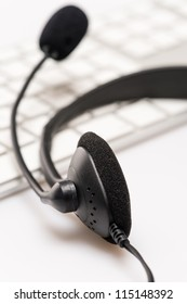 Office headphones with microphone over white keyboard on desk