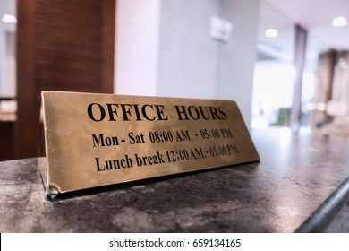 Office Hours gold metal sign on desk for business opening with announcement and give information for customer