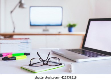 office interior background, glasses on the table, workplace with computer on the desk