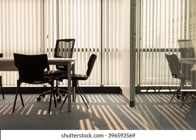 Office interior with light shining through window blinds