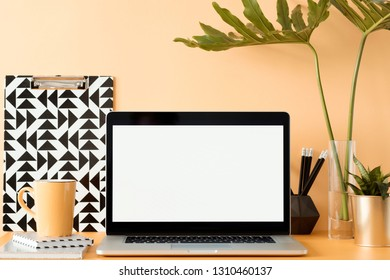 Office interior workspace with laptop mock up screen , office accessories notebook and flowers on the orange background wall. Place for inscription. Homework, freelance.