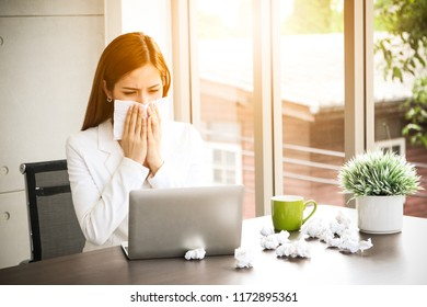 a office lady feeling sick and nasal congestion with snot and sneeze with tissue cleaning