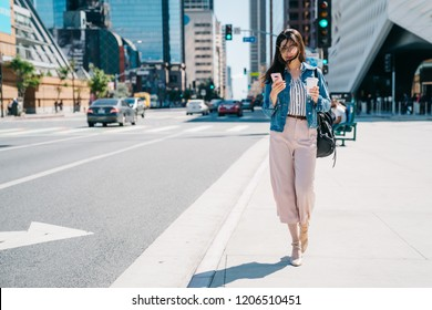 office lady waiting her boyfriend to pick her up beside the road after work. Business woman in motion, calling on mobile smart phone walking outside in city centre. young asian worker lifestyle.