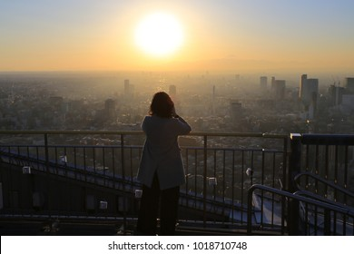 office lady watch the sunset on the top of skyscraper in tokyo