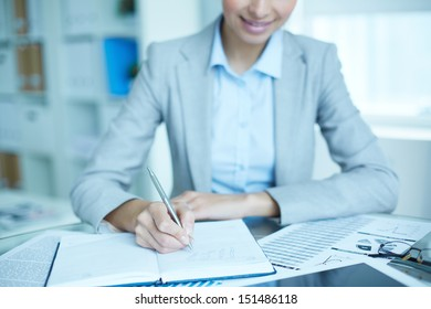 Office lady writing down a week plan in her organizer