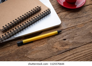 office with laptop and coffee cup pen notepad on the wood table top view shot, Online shopping concept.