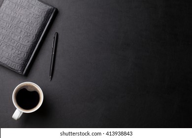 Office leather business desk table with coffee cup, notepad and pen. Top view with copy space