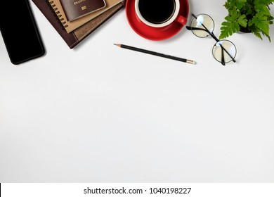 Office leather desk with notebook,eyeglasses, blank screen smartphone, supplies and coffee