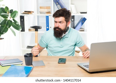 Office life makes him crazy. Businessman with beard and mustache gone mad with hammer in a hand. Angry aggressive businessman in office. Frustrated office worker holding hammer poised ready to smash.