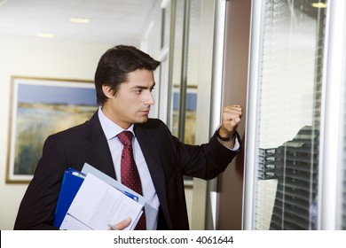 Office life: young employee knocking on his boss door