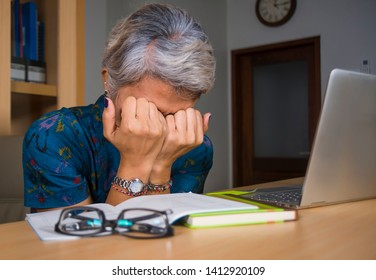 office lifestyle portrait of depressed and overworked middle aged attractive Asian woman working in stress on laptop computer desk covering her face crying overwhelmed looking exhausted