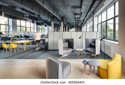 Office in a loft style with large windows, gray walls and concrete columns. There are many workplaces with computers and shelves and lockers, relax zone with armchairs with round tables and lamps.