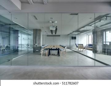 Kantoor in een loftstijl met witte bakstenen muren en betonnen kolommen. Er is een vergaderruimte met een grote houten tafel met grijze stoelen en glazen wanden. Boven de tafel bevindt zich een projector.