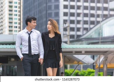 Office lover couple is walking together in a modern city train station