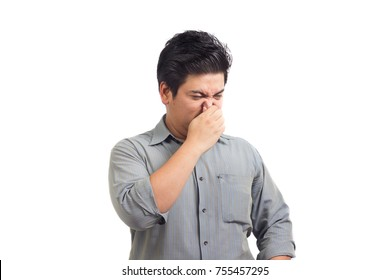 Office man holds or pinches nose shut because of a stinky smell or odor.