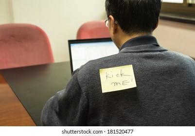 Office man with a yellow sticky note on his back, saying kick me