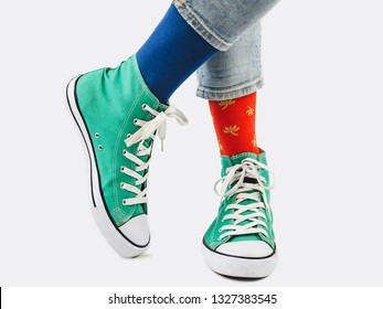 Office Manager, stylish sneakers, blue pants, multicolored, variegated socks. White, isolated background. Close-up. Concept of fashion, fun and elegance